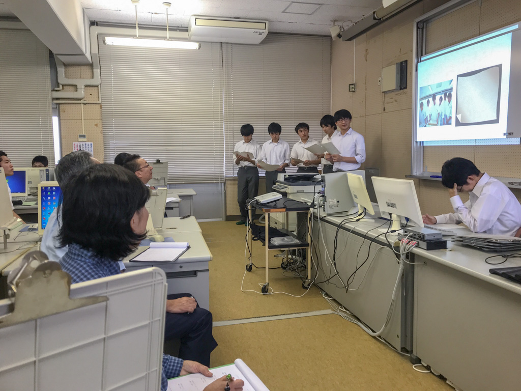 緑峰高校の生徒のプレゼンテーションを受ける先生と民間企業の社長の様子